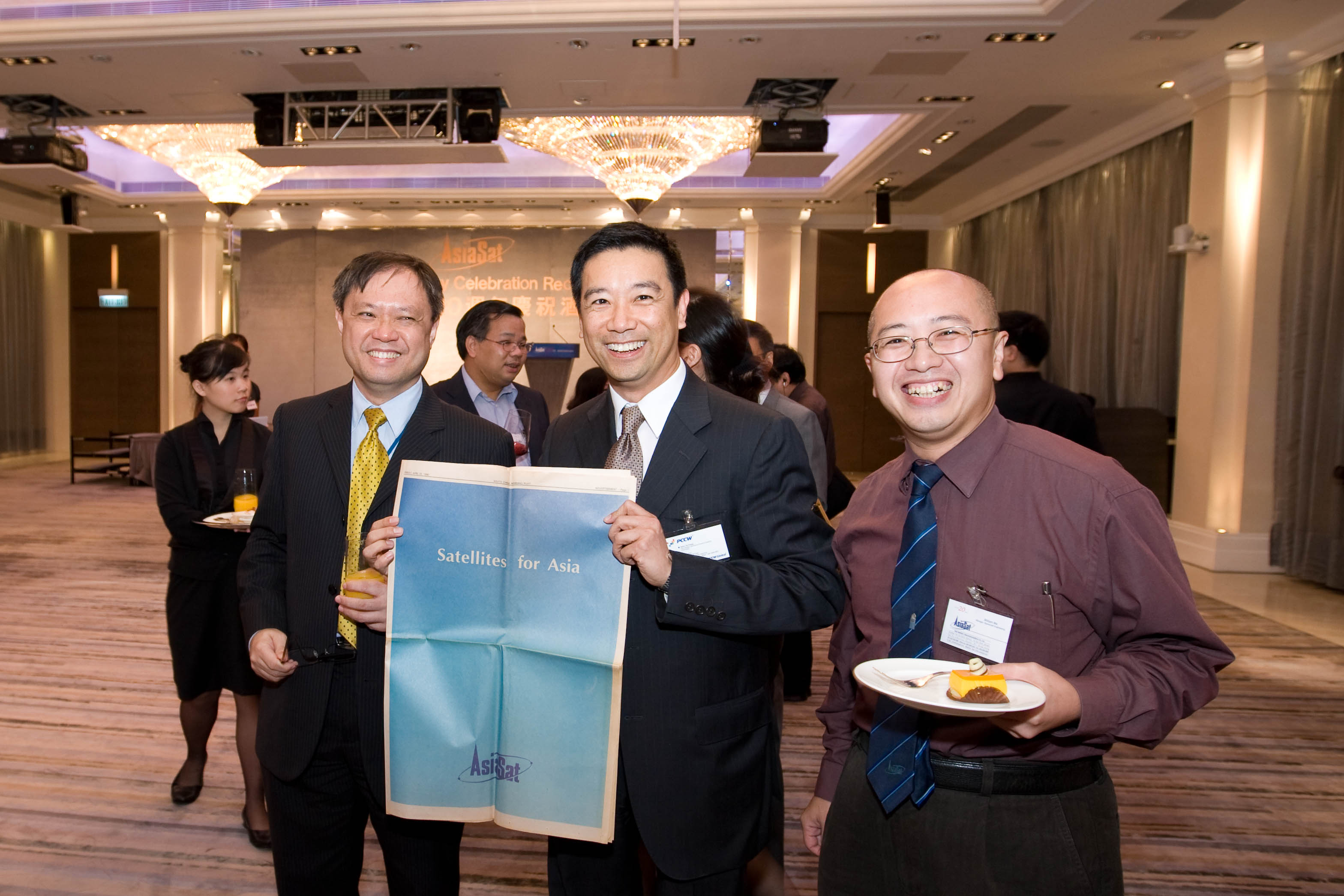 William (right) with Fred Ho (left), AsiaSat's VP Technical Operations and Henry Au Yeung (middle), ex-AsiaSat staff showing a newspaper advertisement commemorating AsiaSat 1 launch during AsiaSat's 20th anniversary celebration cocktail
