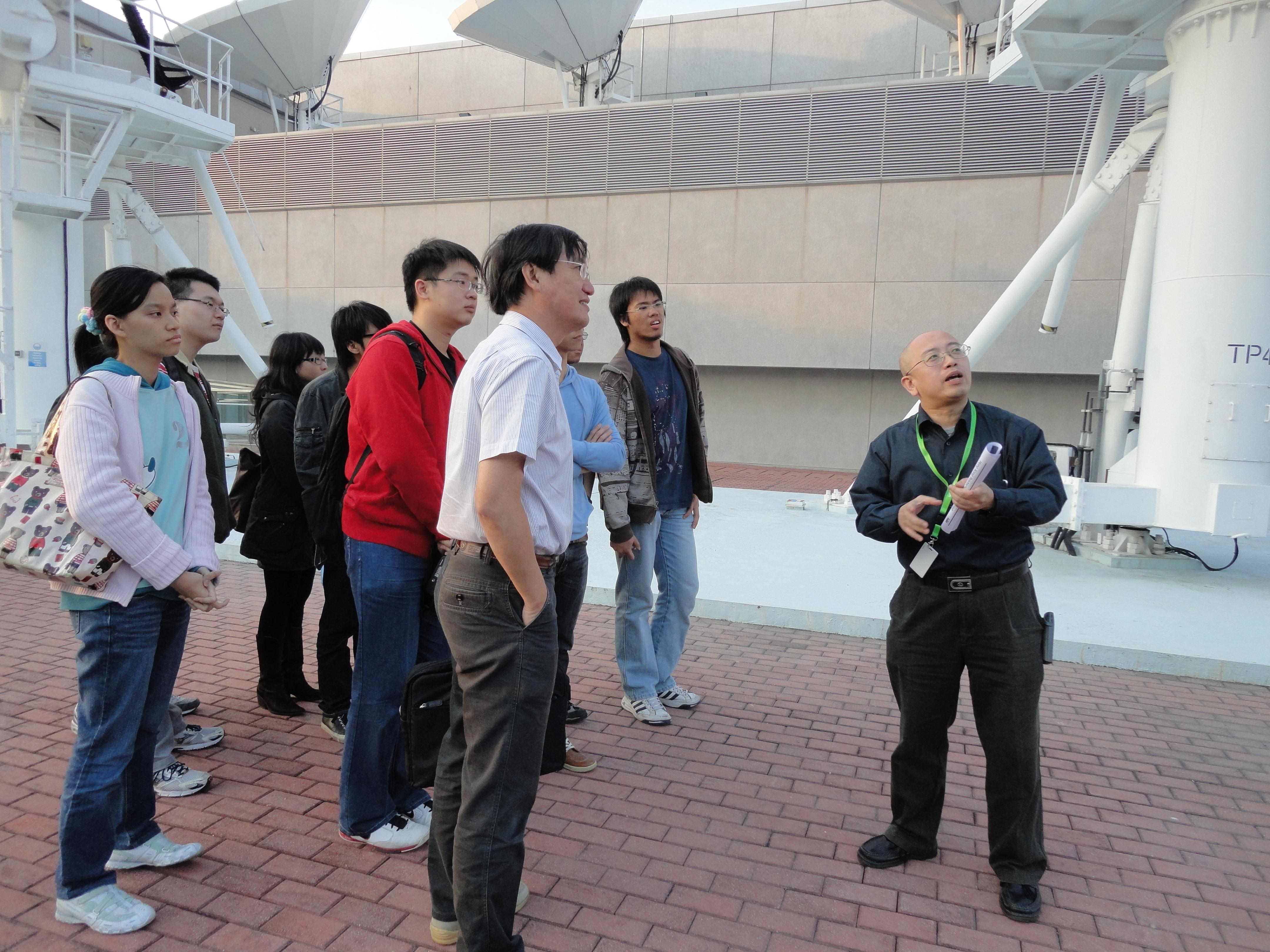 William (right) introducing the satellite control facilities to students visiting AsiaSat Tai Po Earth Station