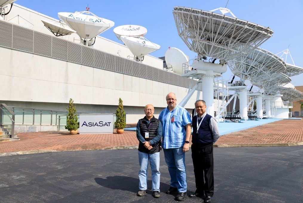 Fred (right) with William Ma (left) introducing AsiaSat Tai Po Earth Station to Anthony Belo of Optus on a sunny day